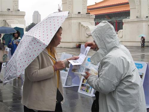 '图5:游客接获法轮大法讯息,仔细阅读。'