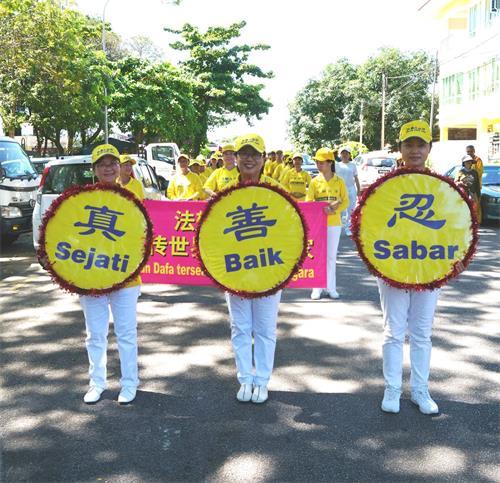 '图12~13:戊戌年大年初十(2月25日),马来西亚法轮功学员来到吉隆坡增江北区(JinjangUtara)举行了第三场新年游行,向当地民众拜年、送祝福,广获各族民众的欢迎。'