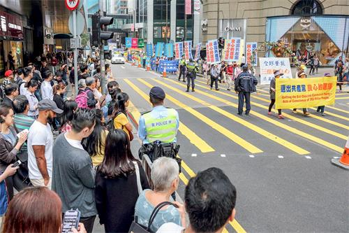 '图6~14:三月十八日下午二时,香港法轮功学员在香港市中心举行游行活动,庆祝并声援近三亿人退出中共党、团、队组织,吸引许多香港市民和大陆游客驻足观看。'