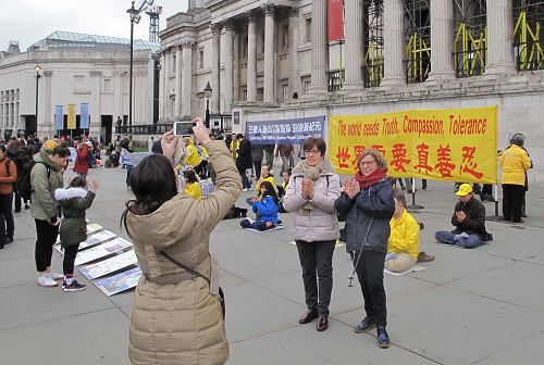 图10:二零一八年三月二十四日,在伦敦特拉法加广场,三位来自某东欧国家的游客在法轮功学员讲真相现场留影,并签名支持法轮功反迫害。