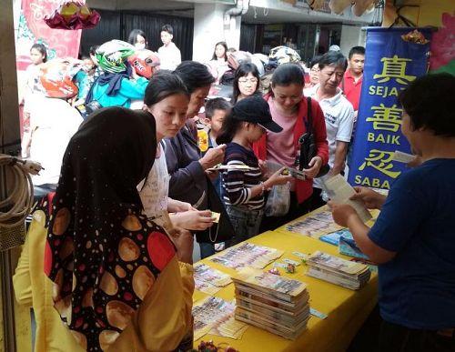 华人聚集区民众在摊位前拿法轮功介绍资料