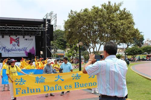 '图9:马海滨马格达莱纳区文化主任何赛先生为法轮功学员拍照'