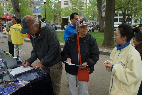图4:法轮功学员(右)讲真相,游客在反活摘请愿书上签字