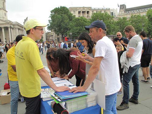 图1~4:二零一八年六月九日,英国法轮功学员在伦敦特拉法加北台阶炼功、讲真相。