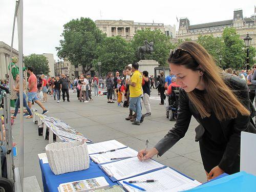 图7:在伦敦读硕士研究生的匈牙利女孩马里亚纳·菲力维(Mariana Filive )在特拉法加广场签名支持法轮功反迫害。