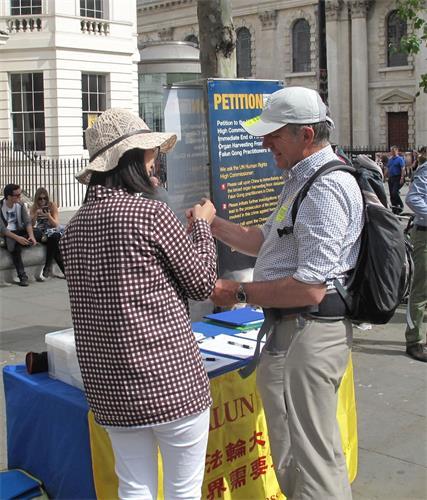 图8:二零一八年六月十二日,在伦敦圣马丁广场,来伦敦参加活动的彼得(Peter)听法轮功学员讲真相,非常高兴地接过法轮功学员送给他的手工莲花。