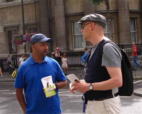 图9:二零一八年六月十二日,在伦敦圣马丁广场,从比利时安特卫普来伦敦旅游的保罗(Paul,右)与遇到的法轮功学员交谈。