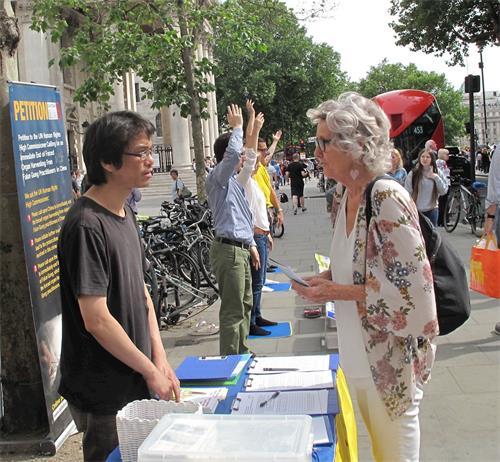 图10:二零一八年六月十二日,在伦敦圣马丁广场,想学功的苏珊(Susan)向法轮功学员深入了解真相。