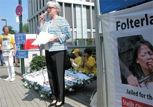 '图3:法轮功学员席费尔(Schiffer)女士在中领馆前朗读了公开信'