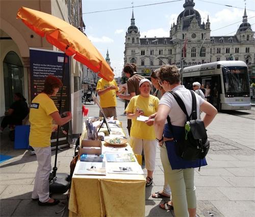 '图1:行人在格拉茨市政厅前的信息展台旁了解法轮功真相'