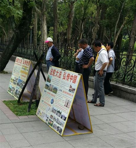 '图1~2:游客在台湾台北国父纪念馆前的法轮功真相点上认真阅读展板'