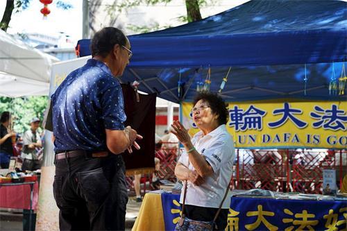 '图1~3:法轮功学员在波士顿中国城主街联欢会上向游客讲真相'