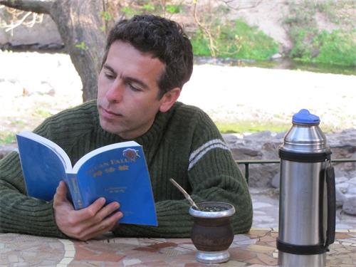 '图1:正在阅读《转法轮》的里卡多·由里(Ricardo?Juri)'