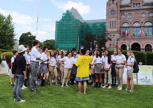 图4:明慧学校老师索尼娅(中间穿黄衣服者)给巧遇的一所学校夏令营的学生们介绍了法轮功。