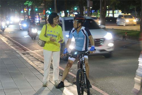 '图4:法轮功学员正在向一位停下脚步关注的自行车骑士解说活动意义。'