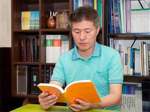 ''图1:李惇荣律师在读法轮大法书籍。''