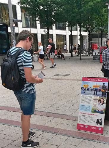 '图9:这位男士正在认真阅读展板,了解什么是法轮功,以及在中国中共对法轮功学员的迫害真相。'