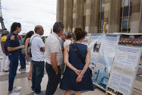 '图1~2:巴黎人权广场上,过往游客认真阅读法轮功真相展板'