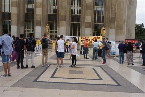 '图3:巴黎人权广场上,过往游客认真阅读法轮功真相展板,观看法轮功学员炼功。'