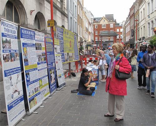 '图1~2:二零一八年八月十一日,法轮功学员在伦敦唐人街炼功、发真相传单、征签反迫害'