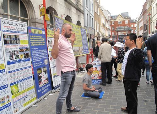 '图5:二零一八年八月十一日,在伦敦法轮功学员杰克帮助下,欧洲男士拉菲尔(Rafael,左)第一次尝试法轮功<span class='voca' kid='86'>功法</span>'
