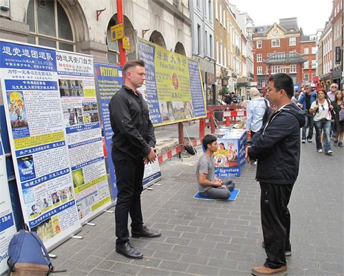 '图6:二零一八年八月十一日,在伦敦法轮功学员杰克帮助下,一位来自立陶宛的年轻商界人士(左)第一次尝试法轮功功法,惊呼神奇'