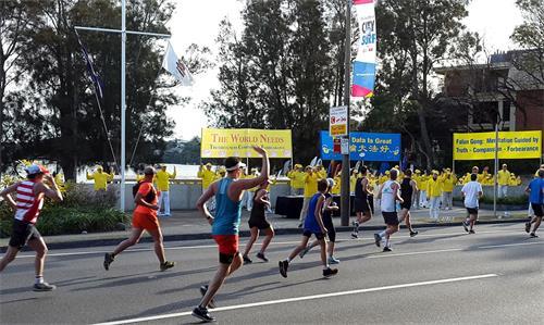 """'图1~2:""""从城市到海滩""""(CitytoSurf)慈善马拉松长跑途中,如潮水般的长跑者汹涌而至与祥和的法轮功学员的晨炼在动静中相映成辉'"""