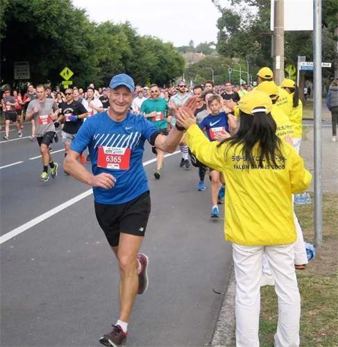 '图3:长跑者经过法轮功学员的活动场地,举起大拇指赞扬。'