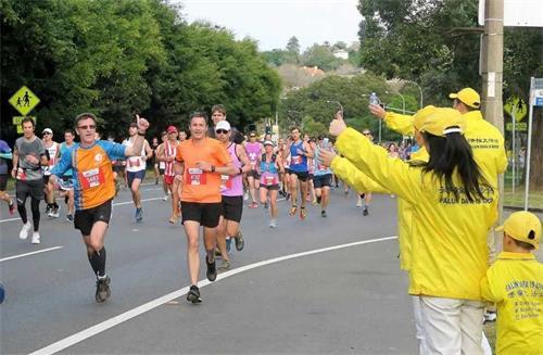 '图4:法轮功学员在街旁与路过的长跑者互动,击掌为他们加油。'