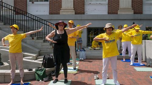 '图:萝丝(前排左二)和法轮功学员一起在在伯灵顿市教堂街炼功。'