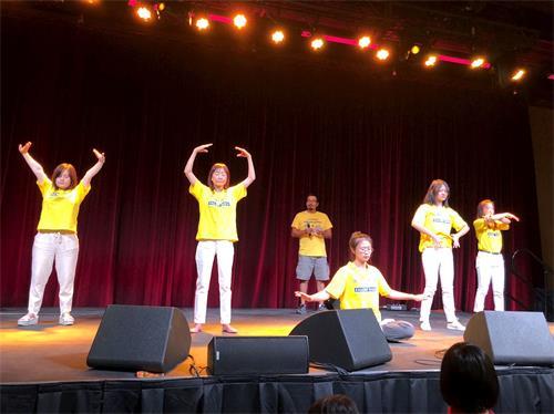 '图6:学员们在舞台上表演五套功法,一名西人学员在讲解;'