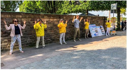 '图1:法轮功学员在斯德哥尔摩市政厅入口处的真相点演示法轮功的五套功法。'