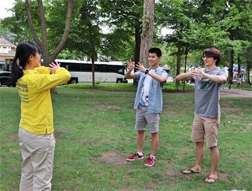 '图14:来自波士顿的大学生柯尔(Cole右)和克里斯(Chris左)正在学炼法轮功功法动作。'