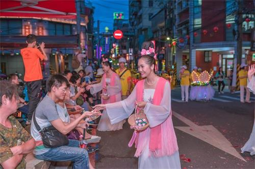 '图3:青年法轮功学员装扮的仙女队向两旁观众发放莲花'