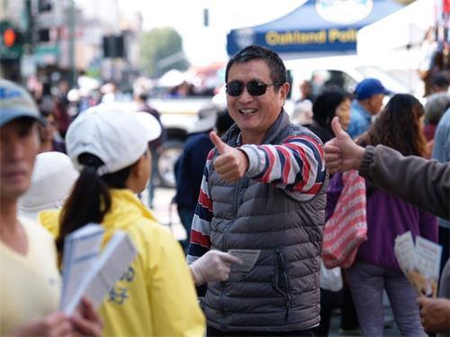 """'图3:这位男士看到身穿印有""""法轮大法好""""字样黄色T恤衫的学员,就对学员竖起大拇指。'"""