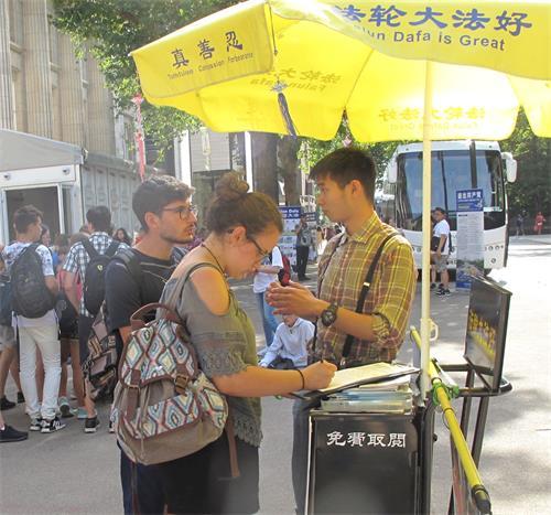 '图2:一对青年游客驻足认真了解真相后签名支持法轮功反迫害'