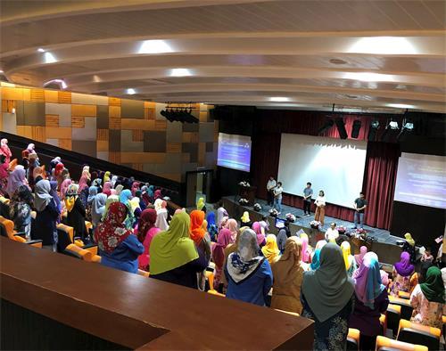 '图1~3:法轮功学员在台上演示功法,上百名来宾们跟着一起学炼,场面十分祥和。'