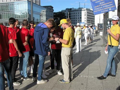 '图6:游行队伍经过之处民众踊跃为反迫害签名'
