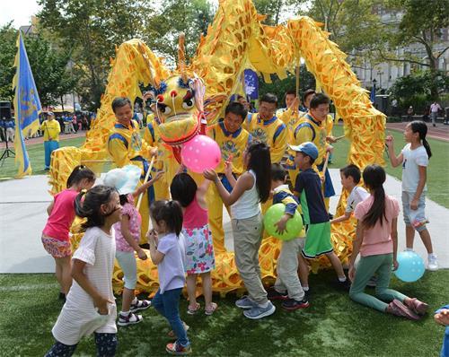 '图2:迎中秋,法轮功学员给纽约华埠民众送祝福。小朋友们特别喜欢精彩的舞龙表演。'