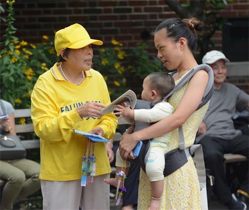 '图3:华人市民接过法轮功真相资料,与法轮功学员交谈。'