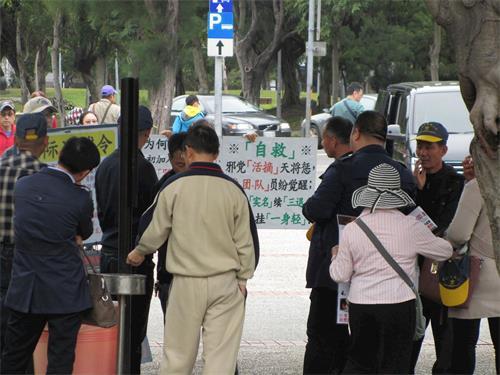 ''图2:中国大陆游客观看法轮功真相展板,聆听学员讲真相。''