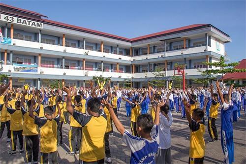 '图1~4:约八百名国中生与老师们在大操场集体学炼法轮功'