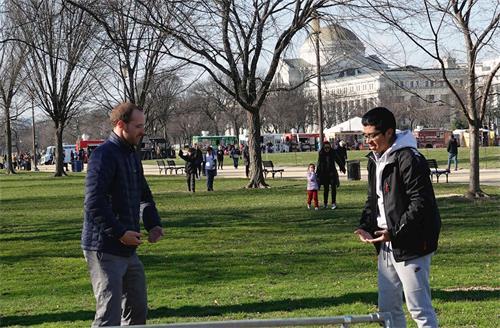 '图2:一位年轻的游客(右)在国家广场学炼法轮功。'