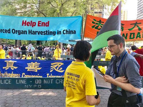 """'图1:福克斯新闻记者亚当·萧(AdamShaw,右)站在""""请帮助结束发生在中国的大屠杀""""(HelpEndGenocideinChina)条幅前,采访法轮功学员简(Jane)。'"""
