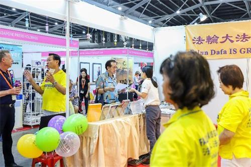 '图1~3:二零一九年十月十一日至十三日,法轮功学员在新加坡博览中心(SingaporeExpo)举办的健康保健展上设立展位,向人们介绍法轮功,并免费教功。'
