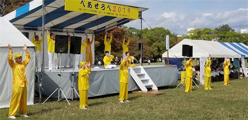'图1:二零一九年十月二十七日,法轮功学员在广岛和平与友爱国际交流节的舞台上演示法轮功五套功法动作。'
