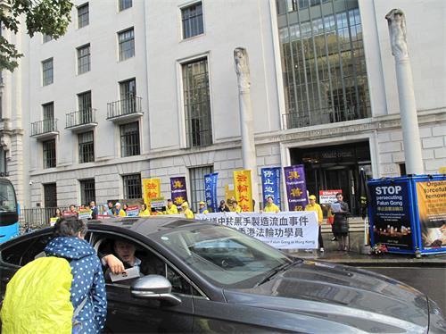 '图3:英国法轮功学员在伦敦中使馆前集会反迫害,路人和司机接过法轮功真相传单。'
