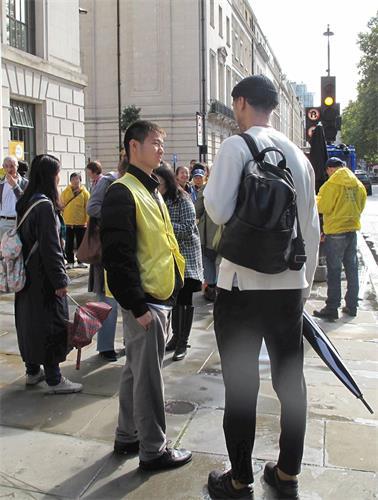 '图5:十月一日,反迫害集会结束后,英国学生约翰(右)与法轮功学员交谈进一步了解真相。'