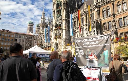 图1:二零一九年十月一日,德国法轮功学员在慕尼黑玛琳广场设立真相点,传播法轮功的真相。披露中共活体摘取法轮功学员器官的大型横幅在闹市中非常醒目。
