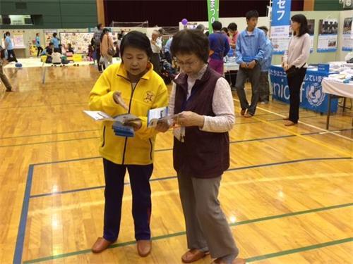 '图1~2:法轮功学员在日本稻泽市福祉宣传活动中向过往的市民介绍功法'